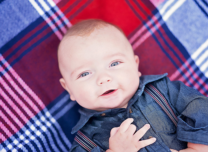 baby laying on red and blue blanket
