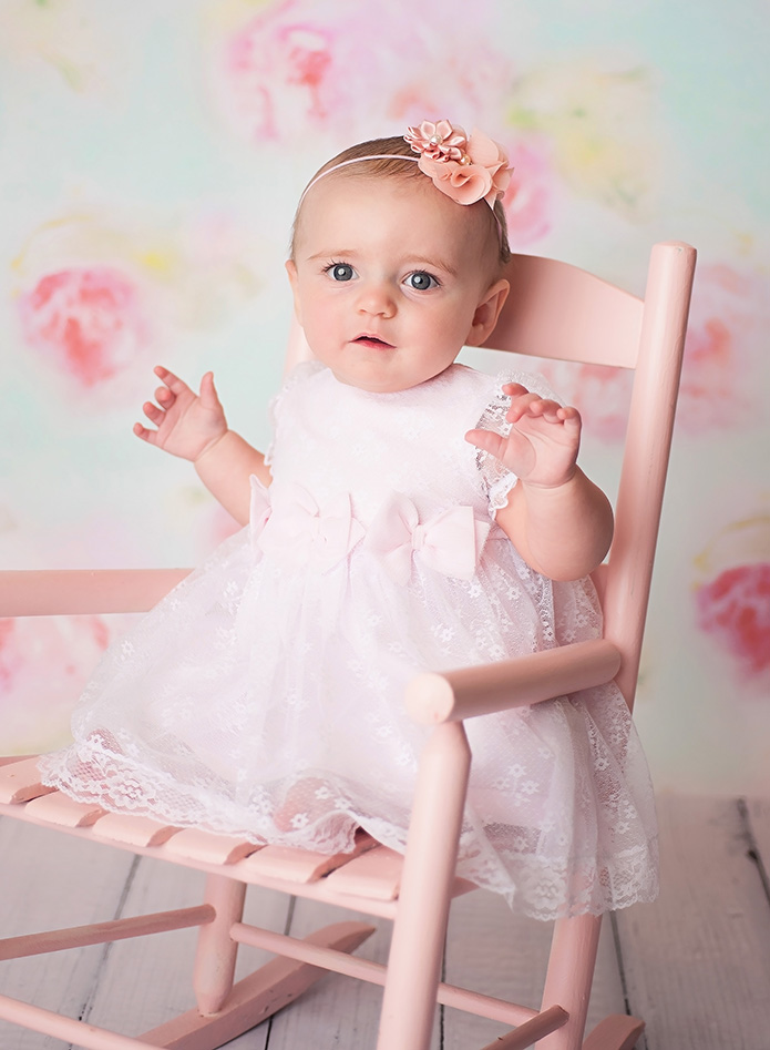 baby girl sitting in pink rocking chair