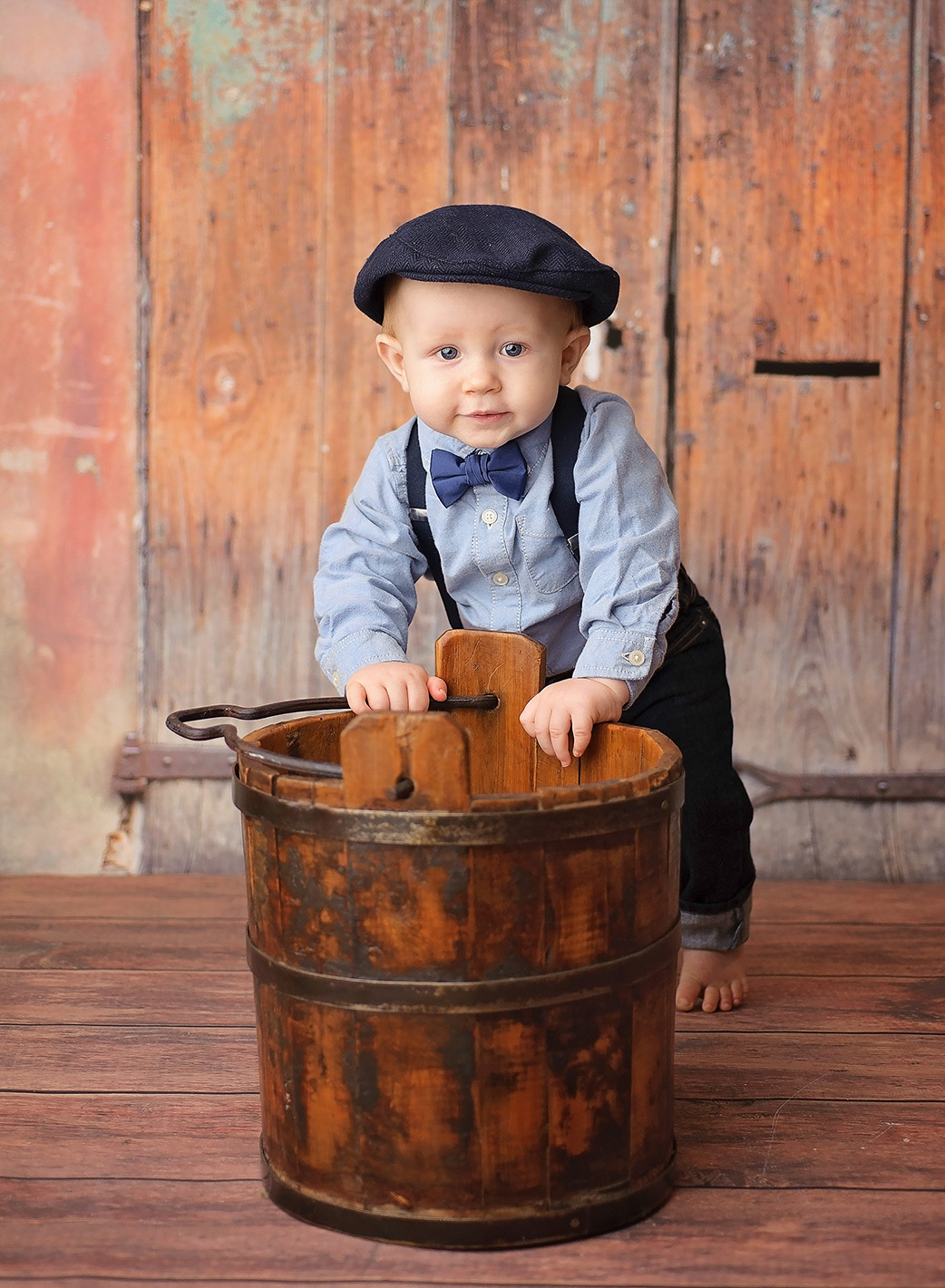 baby boy standing by wood bucket