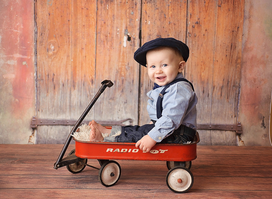 baby boy in red wagonon crate