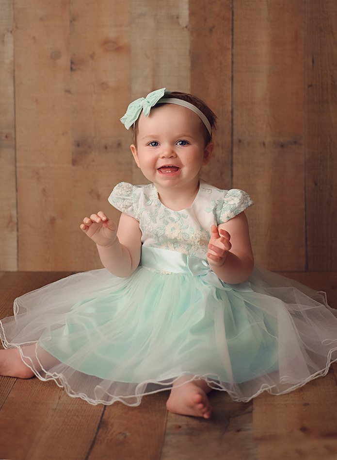 baby girl sitting against wooden backdrop