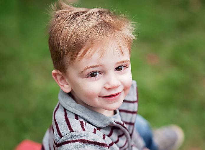 boy in white and red striped shirt smiling
