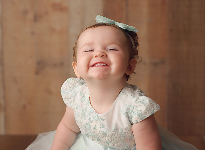 baby girl smiling in blue dress