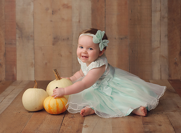 baby grl playing with white pumpkins