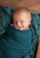 newborn baby wrapped in teal wrap