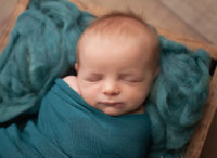 newborn baby snuggled up in a nest of teal wool