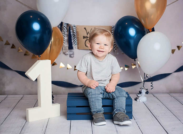 one year old boy sitting on blue crate