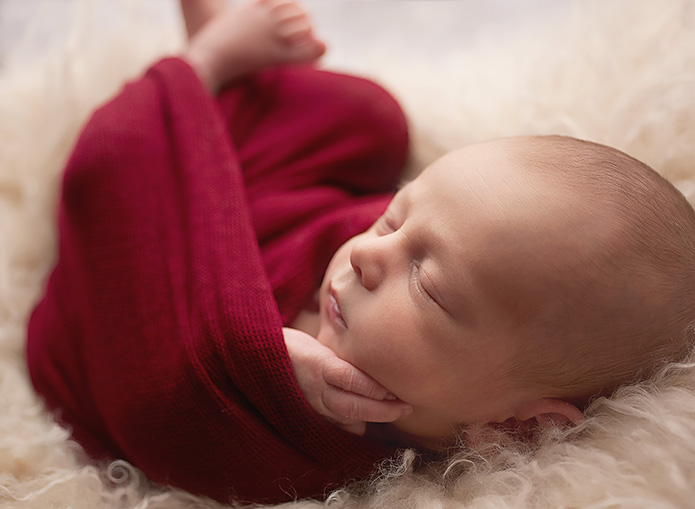 newborn baby wrapped in red