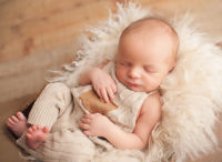 newborn baby boy in overalls laying in white fur