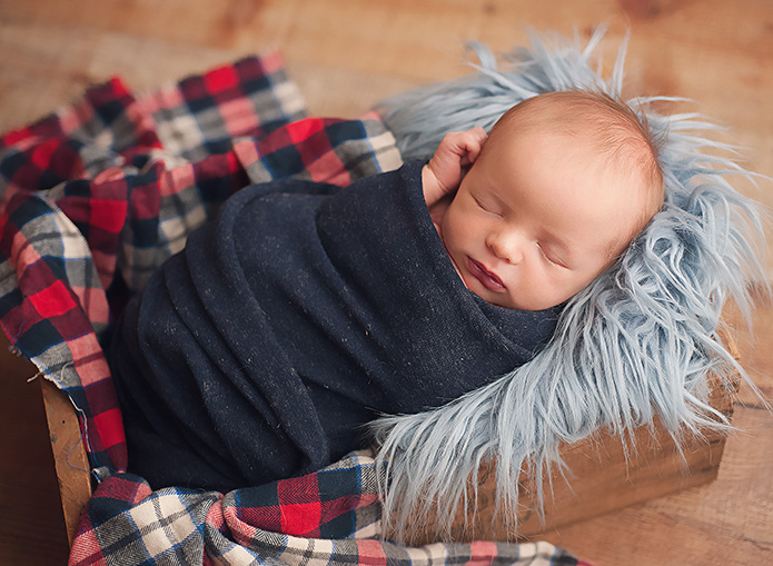 newborn baby boy wrapped in dark blue with blue and red plaid layer