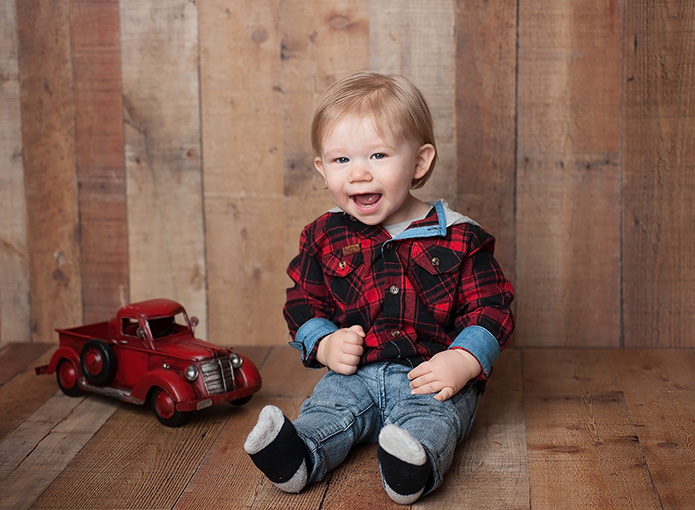 little boy smiling with red truck