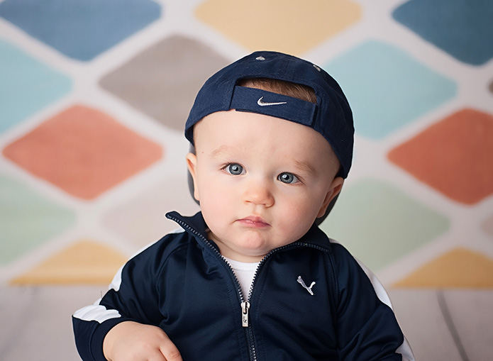 1 year old boy in blue hat against colorful backdrop