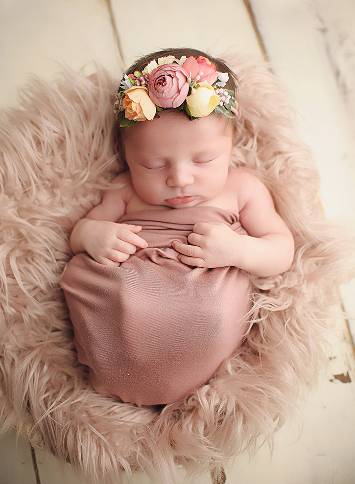 baby with floral headband on laying in pink fur