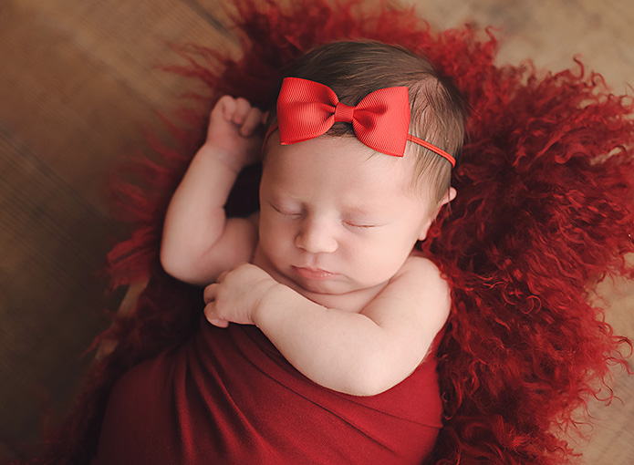 baby girl laying on red fur with red bow