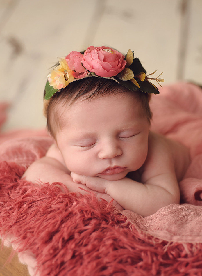 newborn baby girl in crate with pink floral corwn on