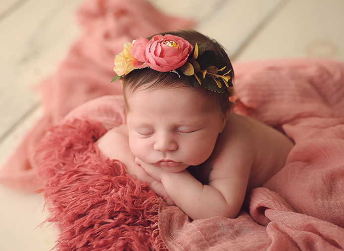 beautiful baby girl laying in wooden box with pink blankets