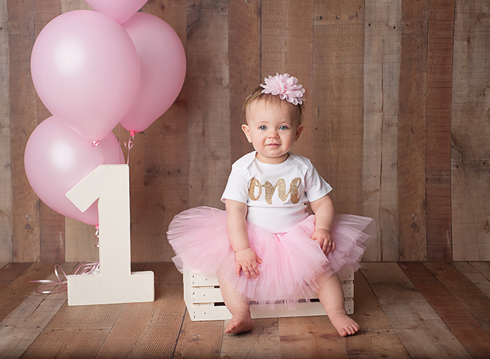 one year old girl sitting on white crate with pink balloons