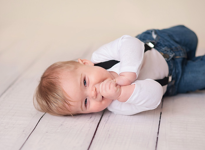 baby boy laying on wooden floor with thumb in mouth