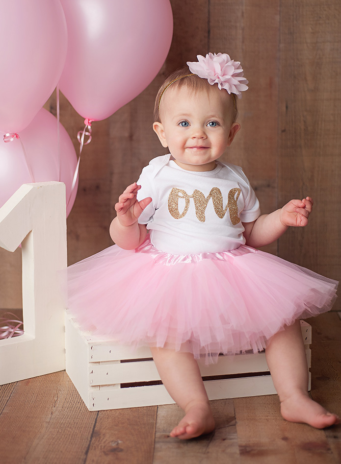 one year old girl sitting on white crate in pink tutu