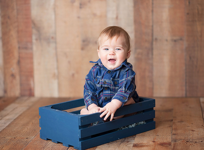 baby boy in blue shirt sitting in navy blue crate