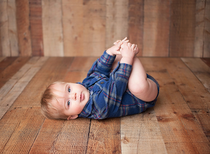 baby boy in blue plaid shirt playing with his feet