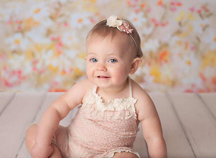 baby girl on white fur with pink romper laughing