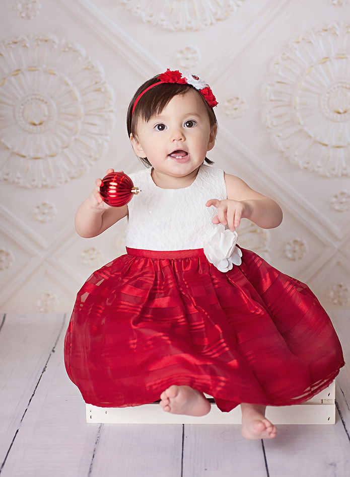 baby girl holding a red christmas ball