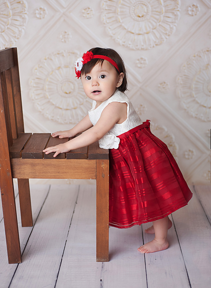 baby girl in her christmas dress standing with a chair