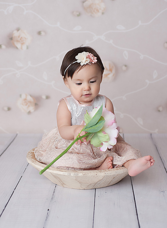 baby girl looking at a pink flower while sitting in a white bowl