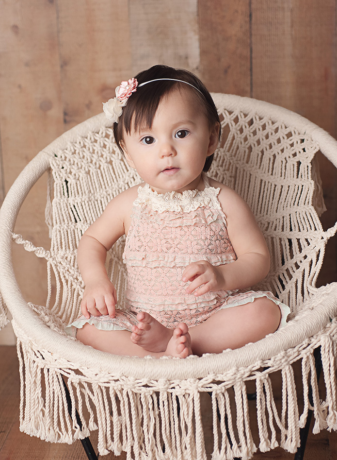 baby girl sitting in a white lacy chair