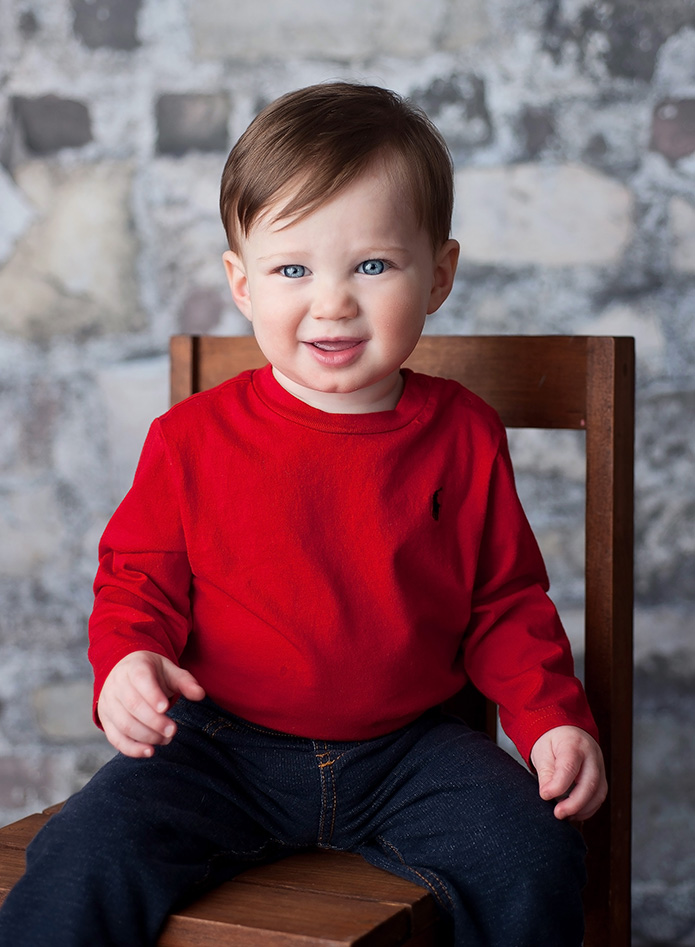 one year old boy in red shirt sitting on chair