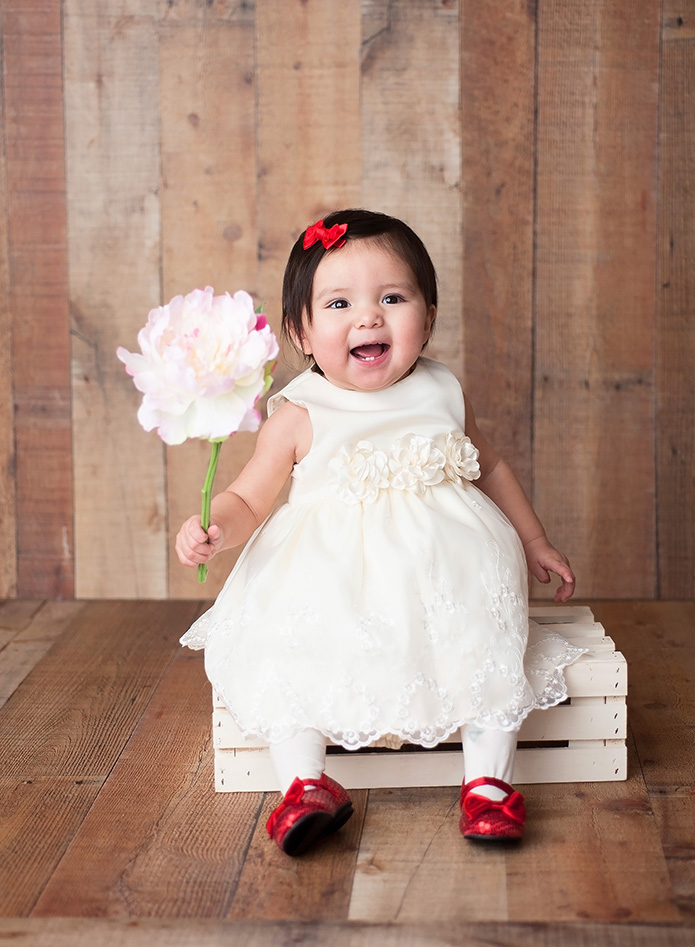 baby girl holding red rose