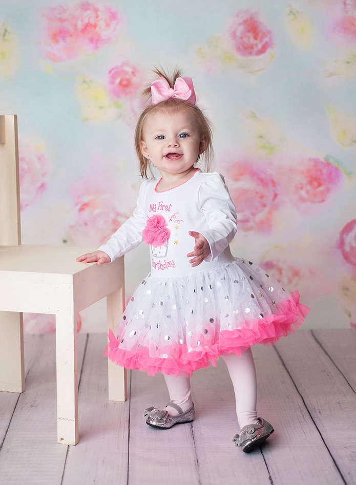 baby girl standing against white chair