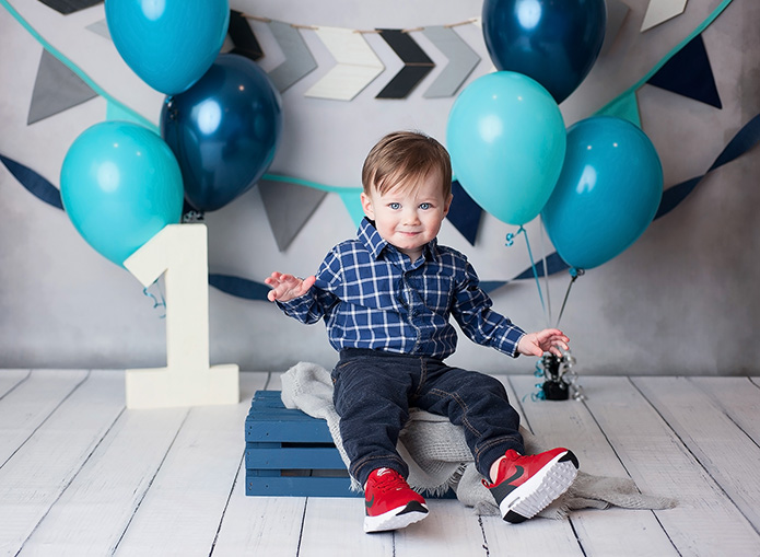 blue first birthday themed backdrop with balloons