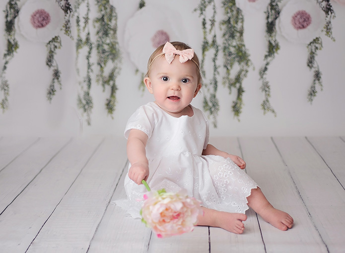 baby girl in white dress agaist floral backdrop