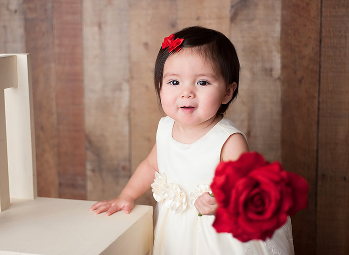 baby girl standing against chair holding rose