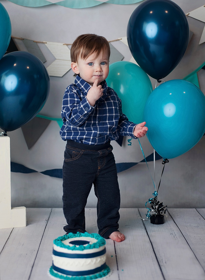 baby boy standing against blue balloons