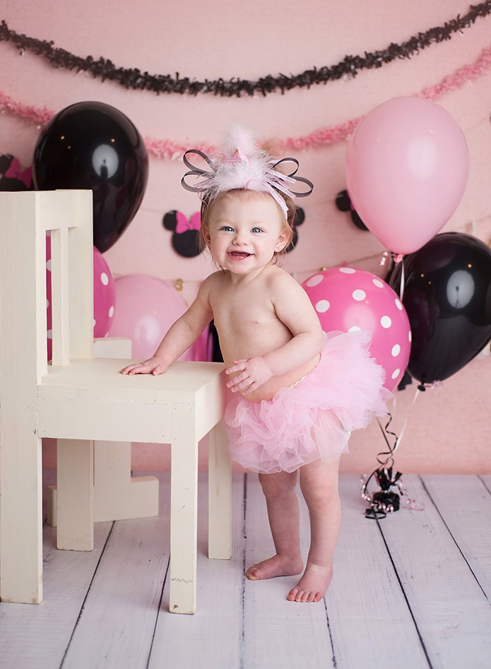 girl in pink tutu standing against white chair