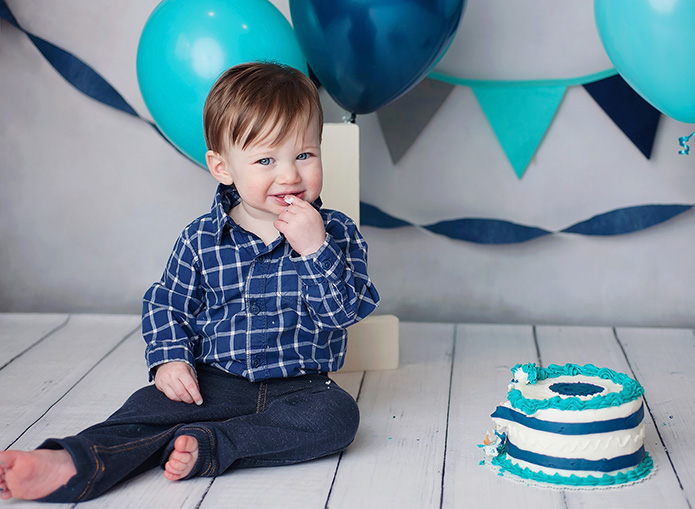 baby boy smiling and eating cake