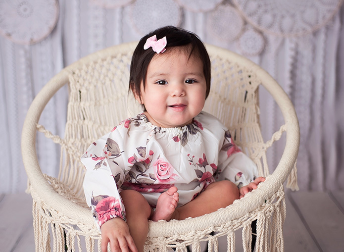 girl sitting in woven chair in floral romper
