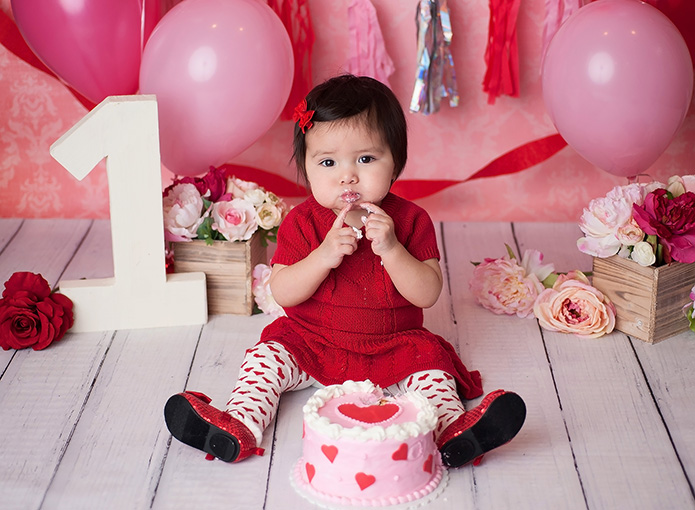 baby girl eating valentines day themed cake