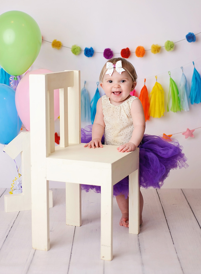 rainbow themed cake smash with baby girl standing against chair